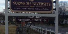 Solider standing in front of Norwich University sign