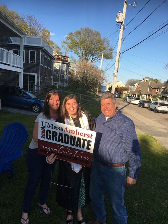 Graduate with her parents posing with UMass Amherst Graduate sign