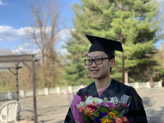 Graduate posing in cap and gown with flowers