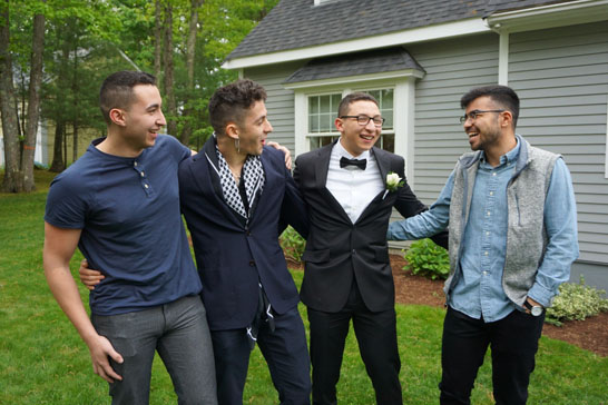 Four men laughing two casual and two in formal attire