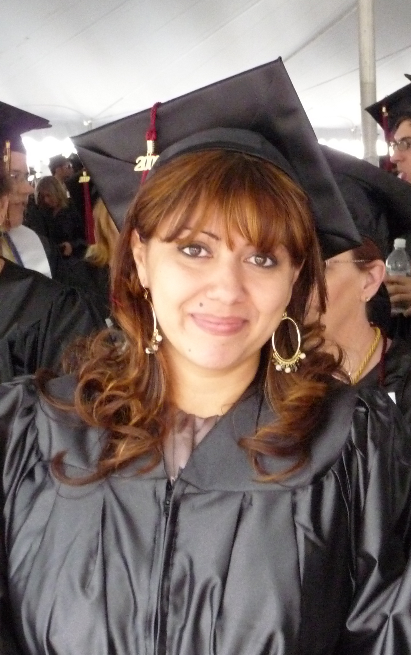 Non-traditional age Latina woman with large, gold earrings, smiling in cap and gown at her college graduation.