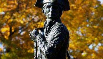 A metal statue of the Minuteman mascot with fall leaves in the background.