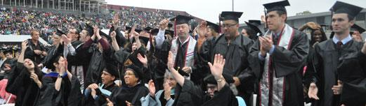 A large, multi-ethnic, diverse group of non-traditional age college graduates standing to be recognized at the UMass Amherst commencement.