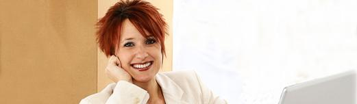 Non-traditional age white women with spiky red hair smiling and sitting among boxes with her laptop.