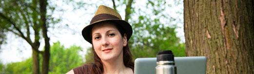 White woman in her twenties wearing a fedora, sitting outside at her lap top surrounded by trees.