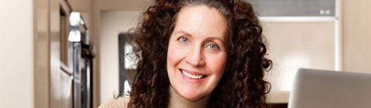 Middle-aged woman with big curly hair smiling with her laptop.