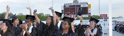 Multi-ethnic group of smiling non-traditional age graduates celebrating at the UMass Amherst commencement.