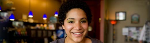 African-American woman with short hair and green eye shadow sitting in a cafe smiling.