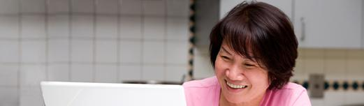 Middle-aged Asian woman in a pink shirt sitting in her white kitchen looking at her laptop while smiling.