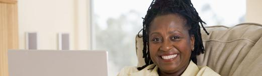 Smiling, older African-American woman with dreadlocks sitting at a laptop.