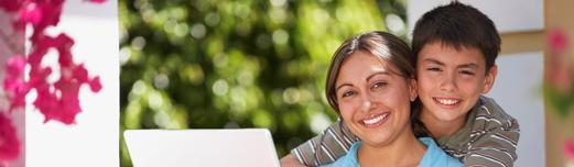 Middled-aged Latina college student on the computer, smiling with her young son