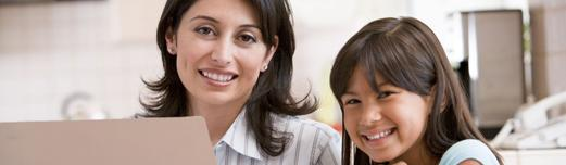 Smiling middle aged Latina woman sitting at a laptop with her daughter.