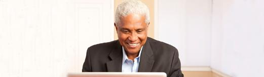 Older African-American man with white hair in a suit jacket smiling while looking at a laptop.