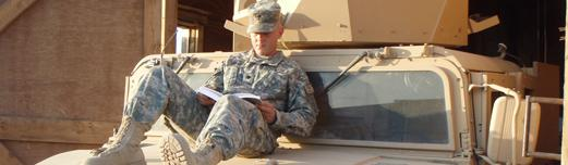 College student in military fatigues sitting on the hood of his jeep reading a textbook.