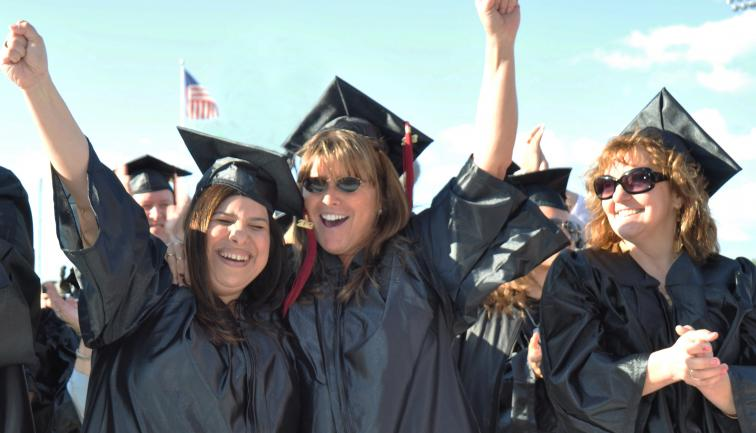 Two middle-aged women in caps and gowns smiling with fists pumped in the air at commencement.