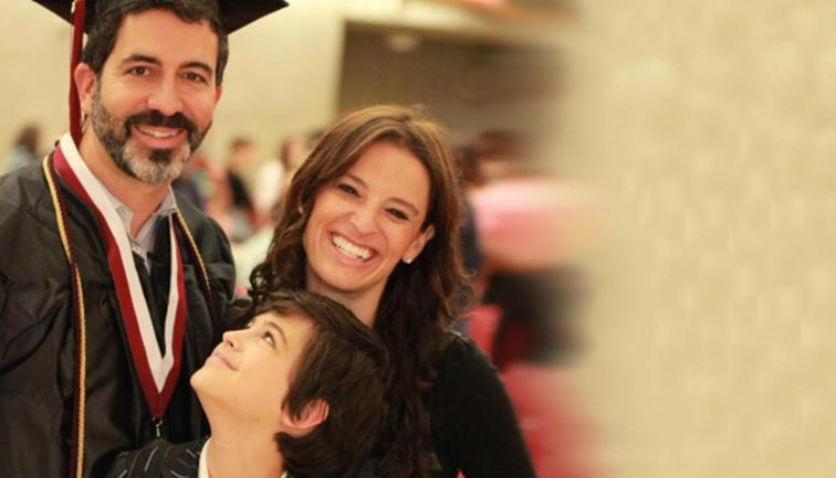Middle-aged college graduate with beard in cap and gown with wife and son