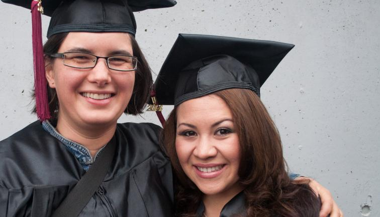 Two woman, non-traditional age college graduates, smiling in caps and gowns.