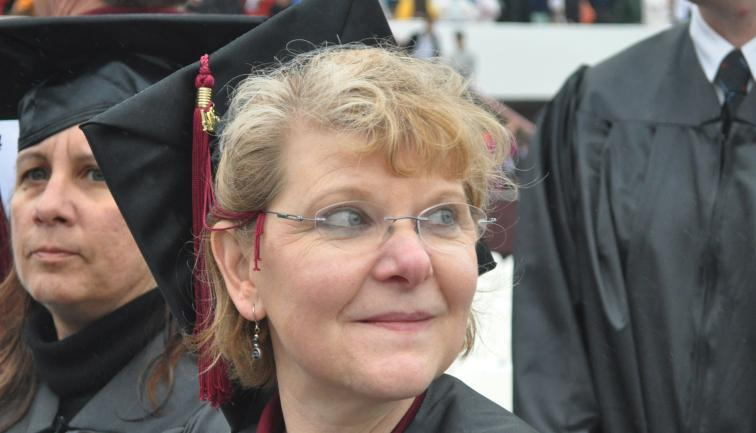 Middle-aged college graduate in cap and gown, smiling and gazing into the stands at commencement.