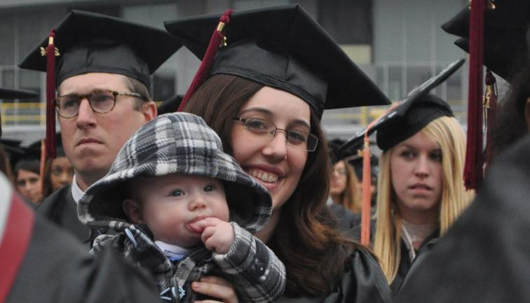 Mother wearing glasses in her cap and gown sitting with her baby at graduation ceremony.