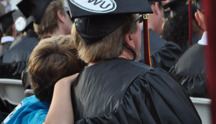 Dad in cap and gown sitting at graduation with his son lovingly leaning on his shoulder.