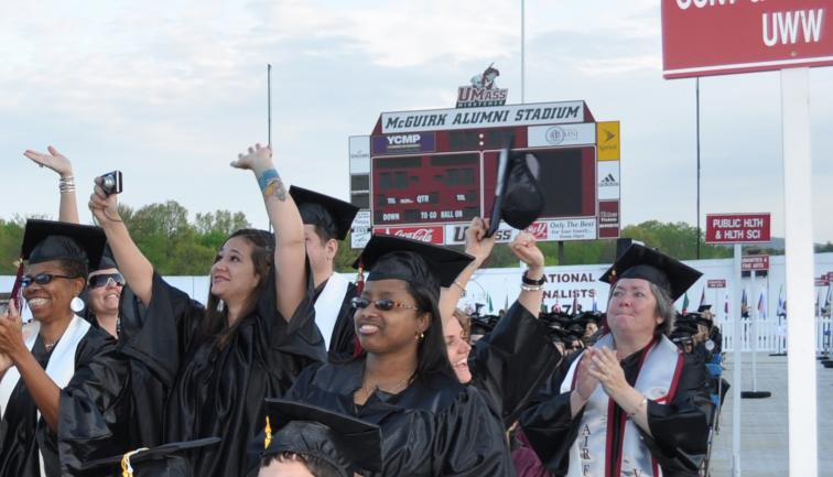 A multi-ethnic group of smiling, older college graduates in caps and gowns.