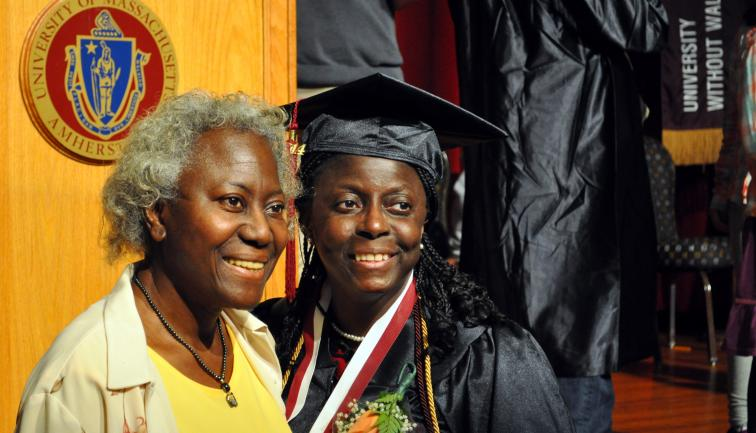 African-American non-traditional age graduate in cap and gown smiling with her mother.