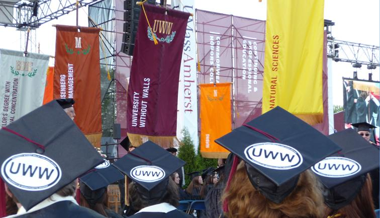 UMass Amherst graduates with UWW stickers on their caps watching the procession of colorful university flags at the commencement ceremony.