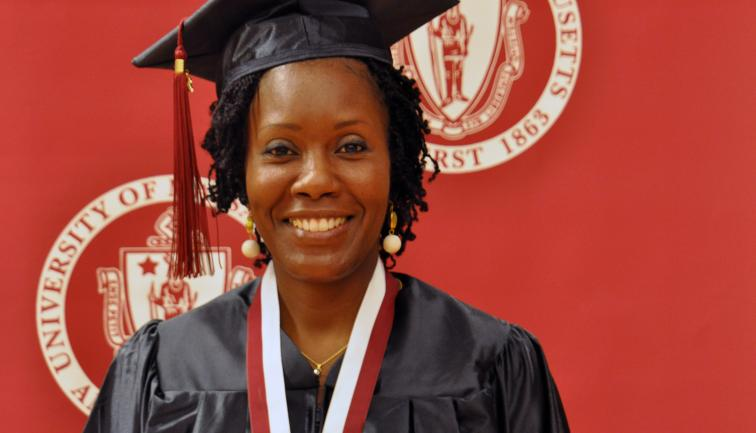 African-American non-traditional age graduate in cap and gown smiling in front of red backdrop and Massachusetts State seal.