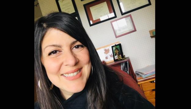 Lisa Modenos smiling, wearing a black shirt and silver hoop earrings. She has long, straight black hair. In the background is a desk and diplomas hanging on a white wall.