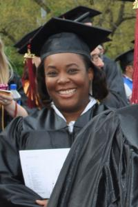 Non-traditional age African-American college graduate smiling, wearing her cap and gown.