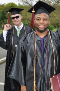 Two male college graduates smiling in their caps and gowns- one white male in his 60's wearing sunglasses and pumping his fist, and one non-traditional age African-American man wearing an honor's cord.