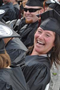 Non-traditional age, white, female college graduate laughing in her cap and gown at commencement.