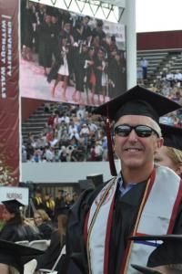 Middle-aged, white male with white hair wearing his cap, gown and veteran's sash, standing and smiling with the crowd behind him at the UMass Amherst commencement ceremony.