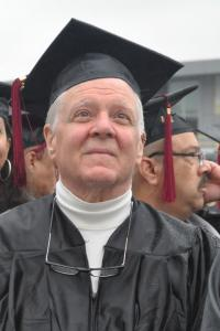 College graduate in his 60's with white hair sitting in his cap and gown.