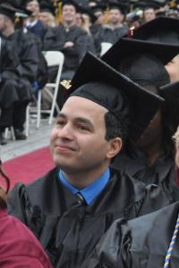 Non-traditional age Latino graduate sitting at commencement in his cap and gown.