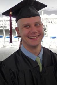 Non-traditional age white male college graduate smiling in his cap and gown.