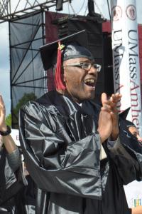 Non-traditional age African-American college graduate wearing a cap and gown, standing and cheering at the UMass Amherst commencement ceremony.