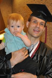 Smiling, non-traditional age college graduate wearing a cap and gown, and holding his baby son.