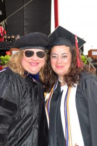 Julie Skogsbergh and one of her graduates dressed in commencement regalia