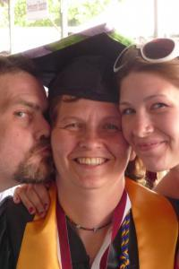 Non-traditional age college graduate smiling in her cap and gown while being kissed on the cheek by her husband and hugged by her adult daughter.