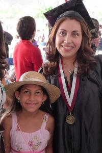 Non-traditional age Latina college graduate in a cap and gown smiling next to a young relative in a pink sundress and straw hat.