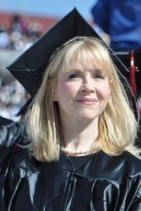 Middle-aged, white woman with blonde hair smiling, standing in the sun, wearing her cap and gown at the UMass Amherst commencement.