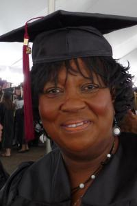 Middle-aged, African-American woman college graduate in her cap and gown.