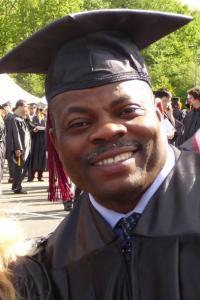 Non-traditional age African-American man smiling while wearing his cap and gown.