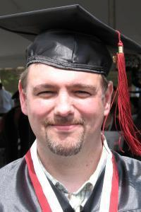 Non-traditional age white male college graduate in cap and gown smiling, standing in the sun.