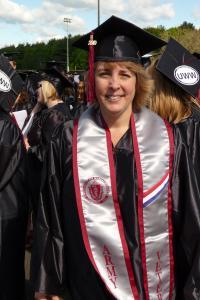Non-traditional age white, female college graduate smiling in her cap and gown, and Army veteran's sash.