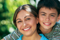 Middled-aged Latina college student smiling with her young son.
