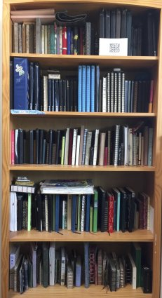 Here is a photograph of five bookshelves filled with hand-crafted diaries.