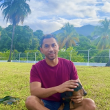 Jarrel De Matas sits in a field with palm trees behind him. He is smiling at the camera and petting a dog.